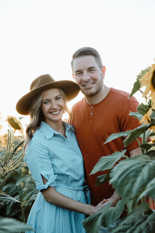 Dr. Ashley Humlicek and her husband standing in a sunflower field