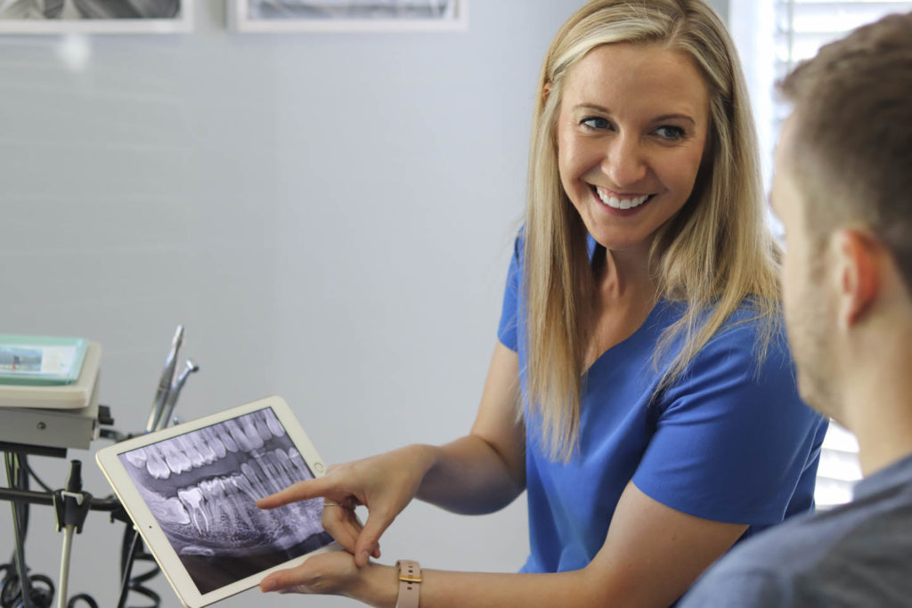 Dr. Ashley Humlicek holds an iPad and discusses dental x-rays with a patient