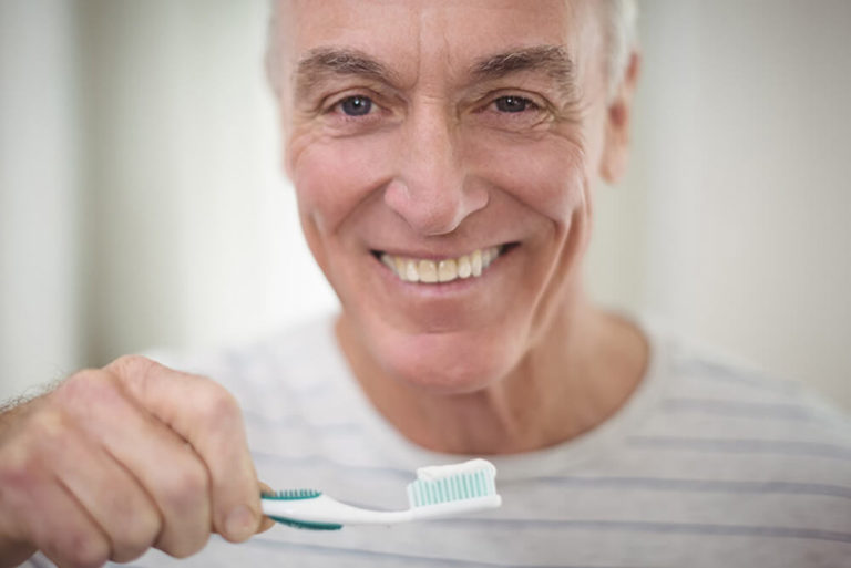 An older man smiles and holds a toothbrush with a glob of toothpaste on it