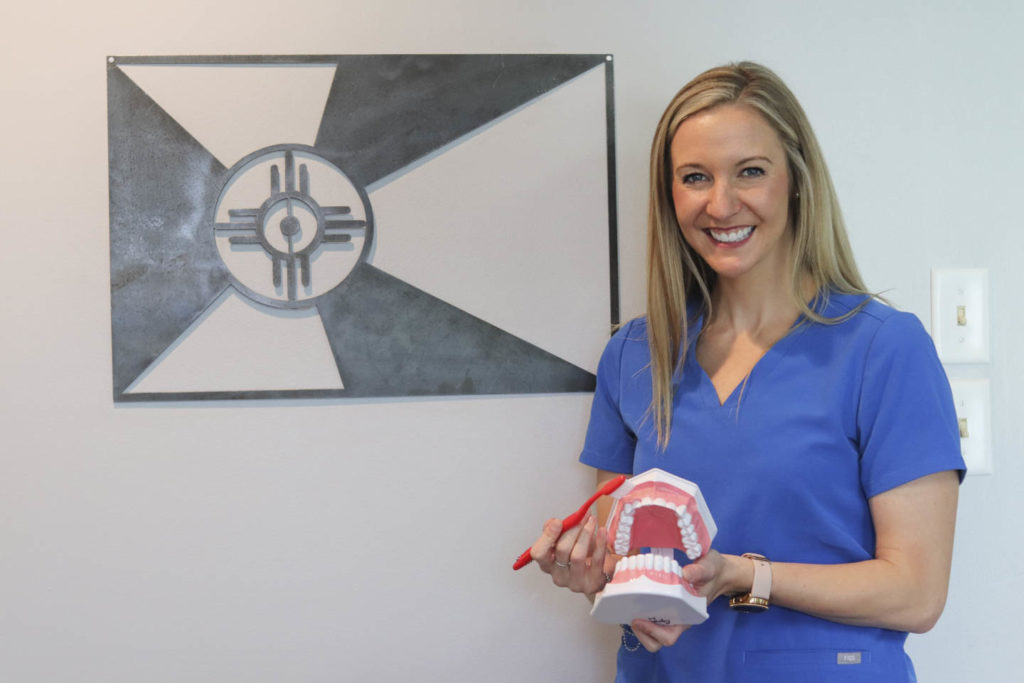 Dr. Ashley Humlicek holding a model of a full set of teeth and a toothbrush