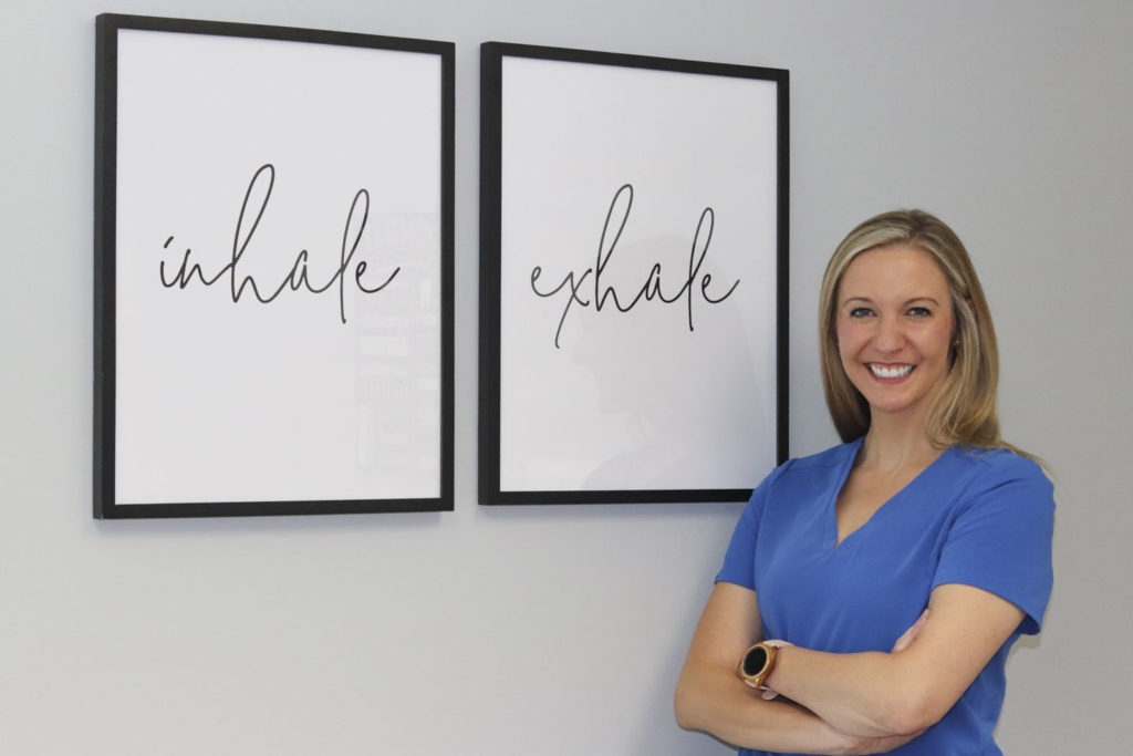 Dr. Ashley Humlicek standing next to wall art that reads Inhale and Exhale at Humlicek Family Dental