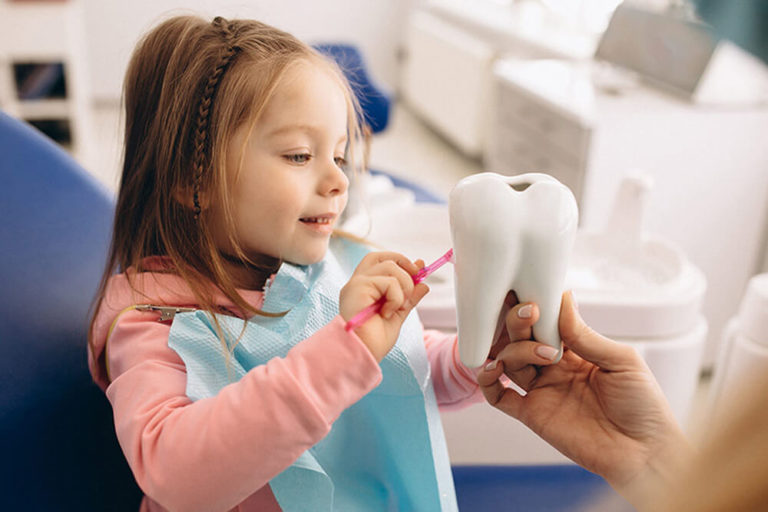 A pediatric dental patient sits in a dental exam chair and brushes a model of a tooth that an out of view adult is holding